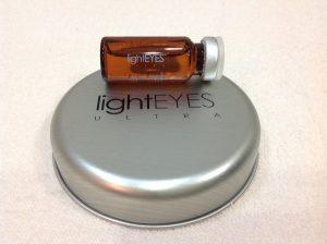 ライトアイズウルトラの褐色のビンがライトアイズウルトラの銀色の丸いケースの上に置かれた画像です