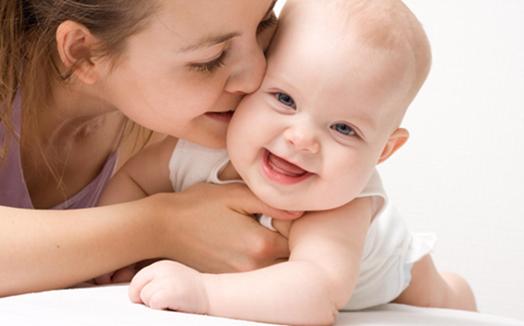 ベビーコラゲン注射の「ベビー」のイメージ画です。真ん中にハイハイしてる白人の赤ちゃんがいて、その右手からホホにキスする女性が写ってます。